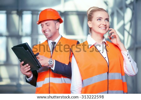 Cheerful female architect is talking on the phone with customer. The project was approved. The foreman is standing near the woman and using a tablet. They are smiling - stock photo