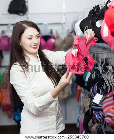 cheerful female buyer choosing bra at clothing store - stock photo
