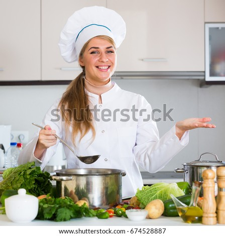 Cheerful female chef making vegetarian meal with vegetables