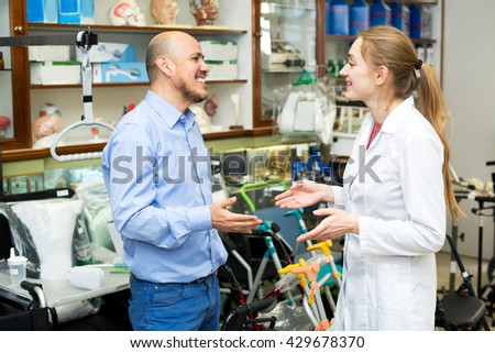 Cheerful female consultant offering wheelchair to mature customer in orthopedic store  - stock photo