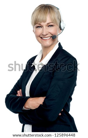 Cheerful female executive wearing headset and posing confidently with folded arms. - stock photo