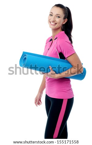 Cheerful female fitness instructor holding mat - stock photo