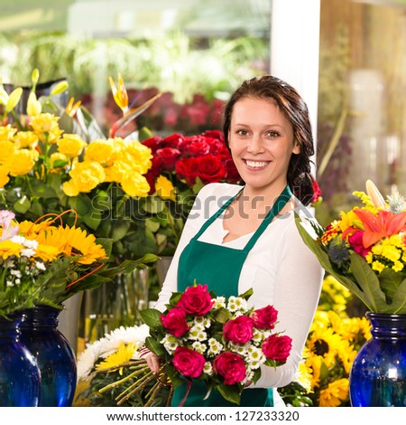 Cheerful female florist bouquet roses flower shop posing owner