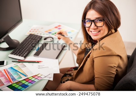 Cheerful female freelance designer doing some work and smiling - stock photo