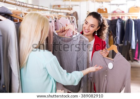 Cheerful female friends choosing new tops in shop and smiling - stock photo