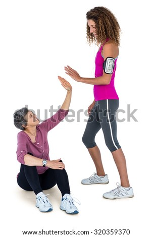 Cheerful female friends high fiving over white background - stock photo