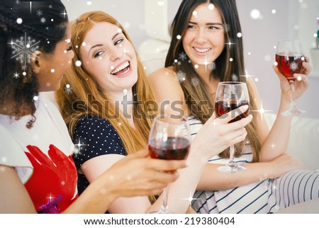 Cheerful female friends with wine glasses enjoying a conversation against snow falling - stock photo