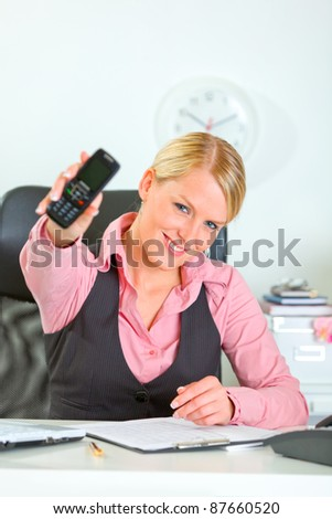 Cheerful female manager showing mobile phone - stock photo