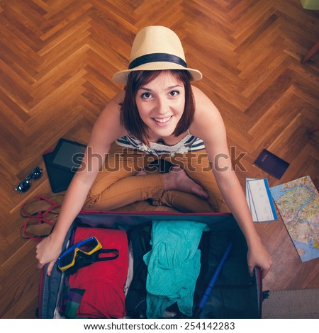 Cheerful Female Packing Suitcase And Getting Ready For Traveling
