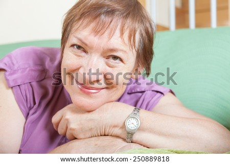 Cheerful female pensioner with violet blouse at home - stock photo