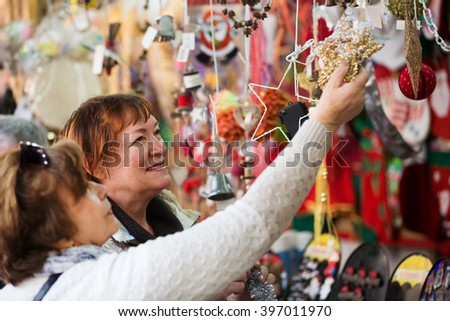 Cheerful female pensioners buying the X-mas decorations and souvenirs at fair  - stock photo