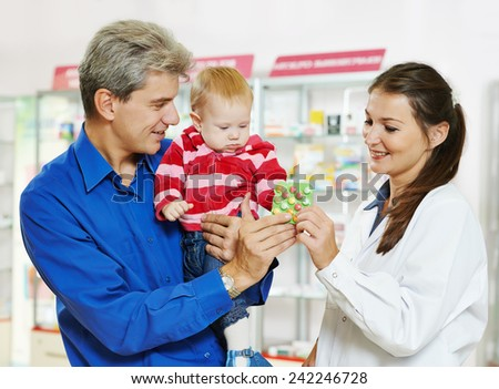 Cheerful female pharmacist chemist showing tablet vitamins to father man with little baby child girl in pharmacy drugstore - stock photo
