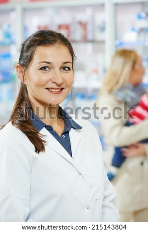 cheerful female pharmacist chemist woman portrait in pharmacy drugstore - stock photo