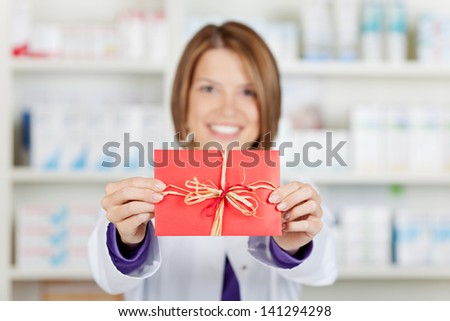 Cheerful female pharmacist showing red card over the drugstore background - stock photo