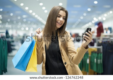 Cheerful female shopper reading a text on mobile phone - stock photo