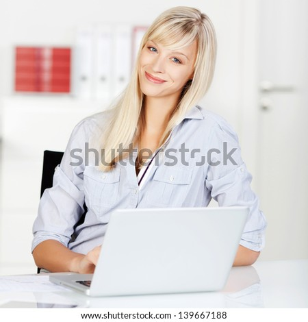 Cheerful female surfing the internet using her laptop