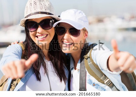 cheerful female tourists giving thumbs up - stock photo