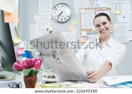 Cheerful female white collar in office desk reading good news on financial newspaper. - stock photo