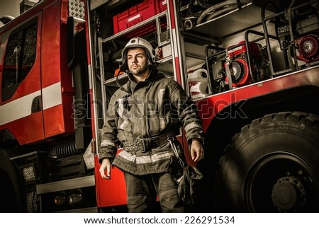 Cheerful firefighter near truck with equipment  - stock photo