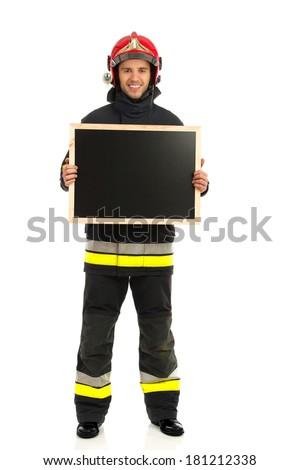 Cheerful fireman in red helmet holding blackboard. Full length studio shot isolated on white. - stock photo