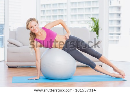 Cheerful fit blonde doing side plank with exercise ball at home in the living room - stock photo