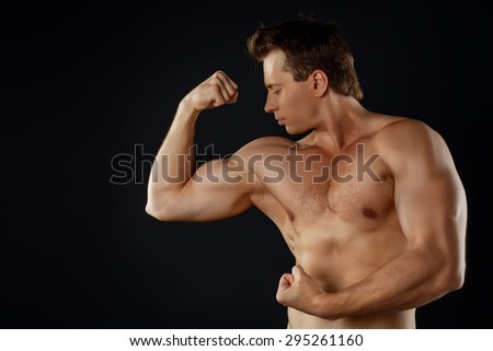 Cheerful fit male athlete is flexing his bicep. His is looking at his left hand with attention. Isolated on black background and there is copy space in left side - stock photo
