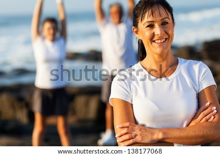 cheerful fit middle aged woman with arms crossed in front of her family on beach - stock photo