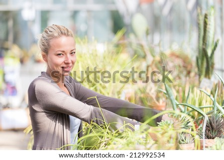 Cheerful florists woman working with topical plants and cacti in a greenhouse.  - stock photo
