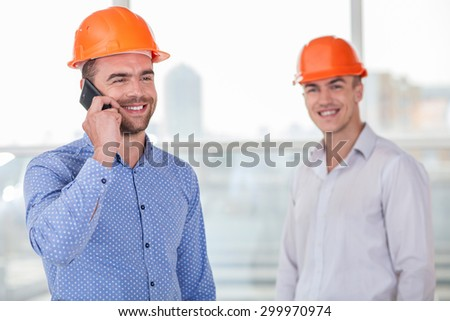 Cheerful foreman is standing on the forefront and talking on the phone with customer. The plan was approved. A worker in helmet is standing near him with happiness. They are smiling - stock photo
