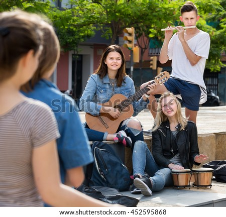 Cheerful four friends teenagers with musical instruments together outdoors - stock photo