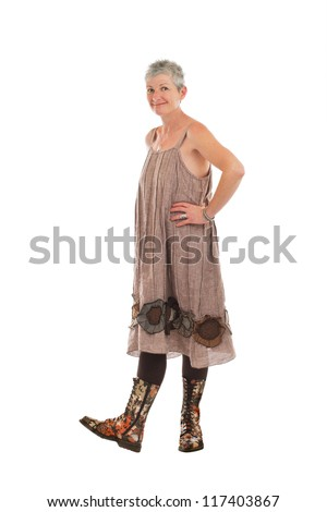 Cheerful friendly older woman stands in flowered boots and brown cotton shift dress. She has short gray hair. Isolated on white background, vertical.