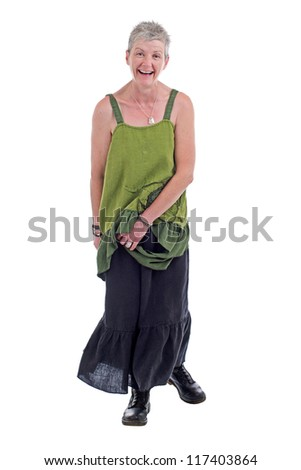 Cheerful friendly older woman stands in loose flowing long green linen two piece dress with ruffle. She has short gray hair. Isolated on white background, vertical. - stock photo