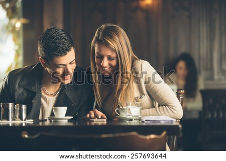 Cheerful friends at the cafe connecting to internet with a smart phone - stock photo