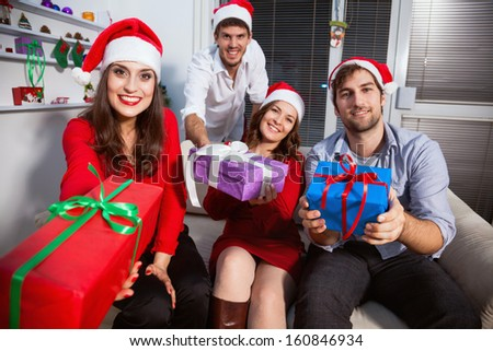 Cheerful friends exchanging presents at Christmas eve - stock photo
