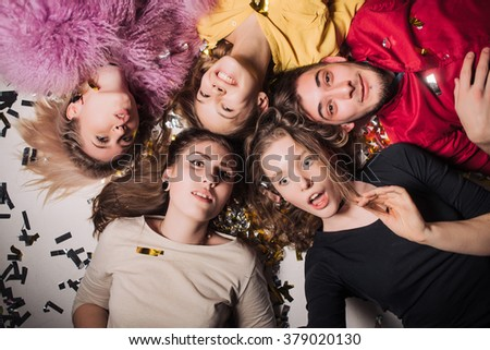 Cheerful friends lying on the floor in nightclub