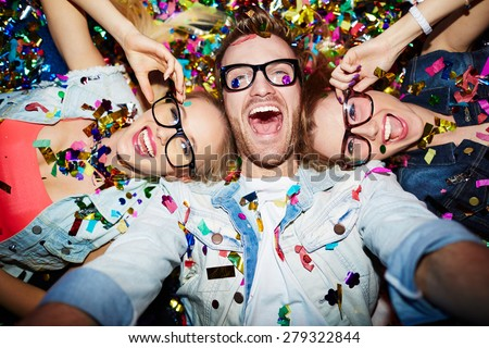 Cheerful friends lying on the floor in nightclub and making selfie