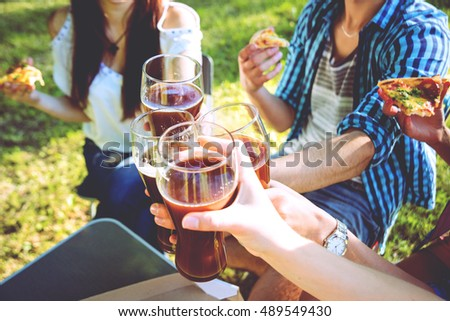 Cheerful friends on picnic in the park. Drinking beer