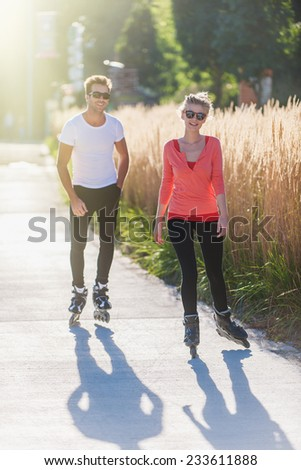 Cheerful friends practicing rollerblading in town on the morning - stock photo