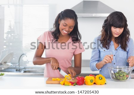 Cheerful friends preparing a salad together at home in kitchen - stock photo