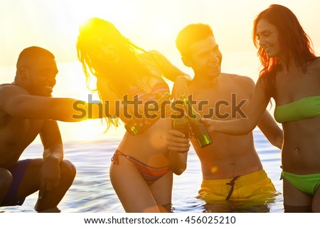 Cheerful friends sitting on their knees while having party on the beach at sunrise- Multi-ethnic young people toasting with beer bottles - Vacation and friendship concept - Sun original color tones