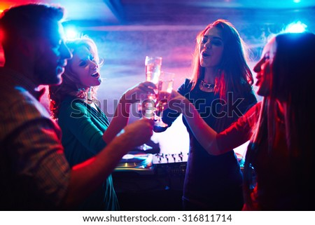 Cheerful friends toasting at party in night club