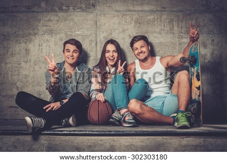 Cheerful friends with with skateboard and ball outdoors - stock photo