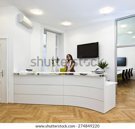 Cheerful front desk lady doing her job with passion. The black space on the TV-screen could be used for any logos, some label signs or any graphic additions. - stock photo