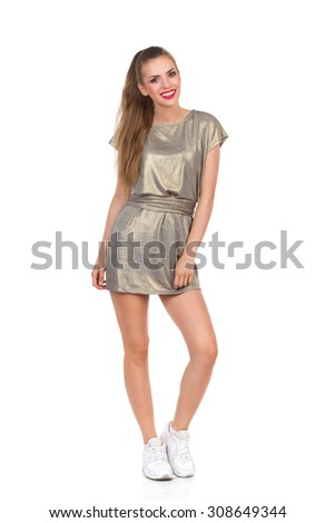 Cheerful Full Length Girl. Smiling young woman in gold mini dress and white sneakers standing. Studio shot isolated on white. - stock photo