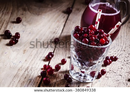 Cheerful funny juice from cranberries, berries with straws in a glass, selective focus - stock photo