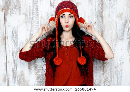 Cheerful funny woman in red knitted warm hat - stock photo