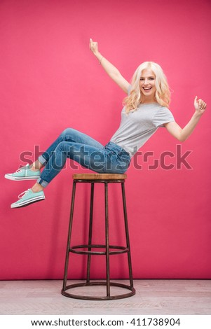 Cheerful funny woman sitting on the chair over pink background and looking at camera - stock photo