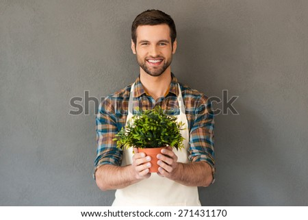 Cheerful gardener. Cheerful young gardener holding flower pot and smiling at camera while standing against grey background  - stock photo