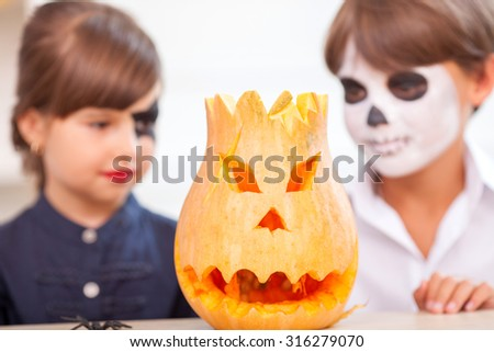 Cheerful girl and boy are looking at the spooky pumpkin with interest. They are sitting at the table and smiling. They have make-up on their faces. Focus on pumpkin - stock photo