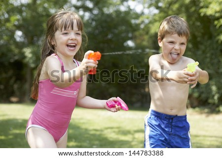 Cheerful girl and boy shooting water pistols in the backyard - stock photo